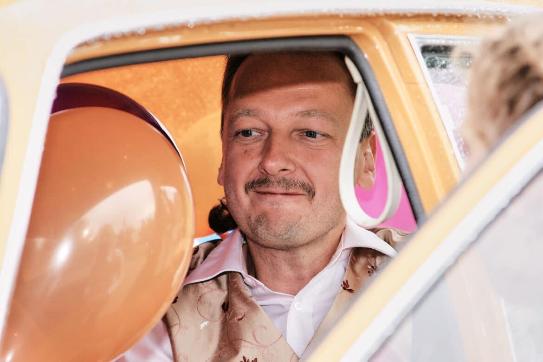 Hochzeitsauto ocker mit Bräutigam sitzend auf Rückbank - Celler Schloss ©Hochzeitsfotograf www.hochzeitsverliebt.de