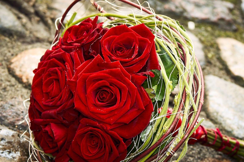 Brautstrauss voller roter Rosen auf Pflasterstein Celler Schloss © Hochzeitsfotograf www.hochzeitsverliebt.de