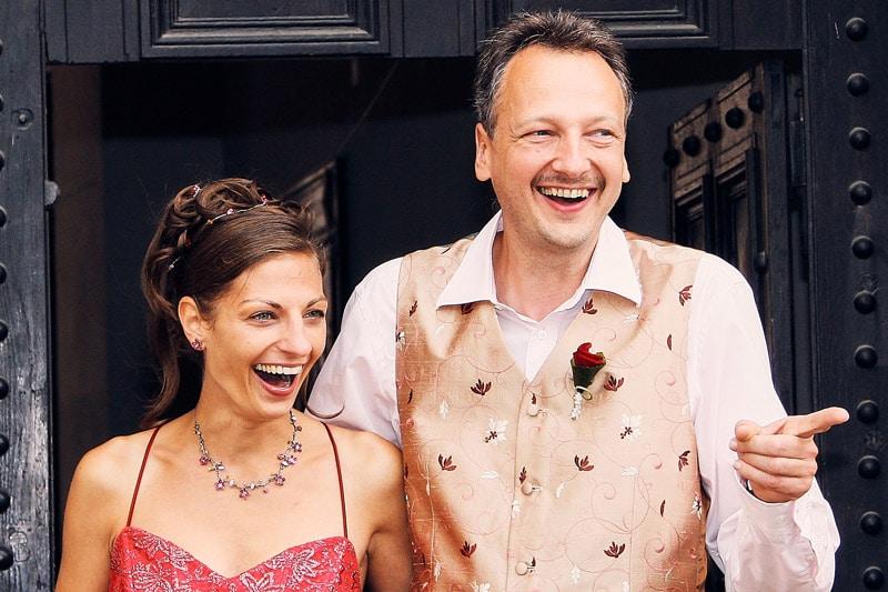 Herzhaft lachendes Brautpaar vor Schlosseingang