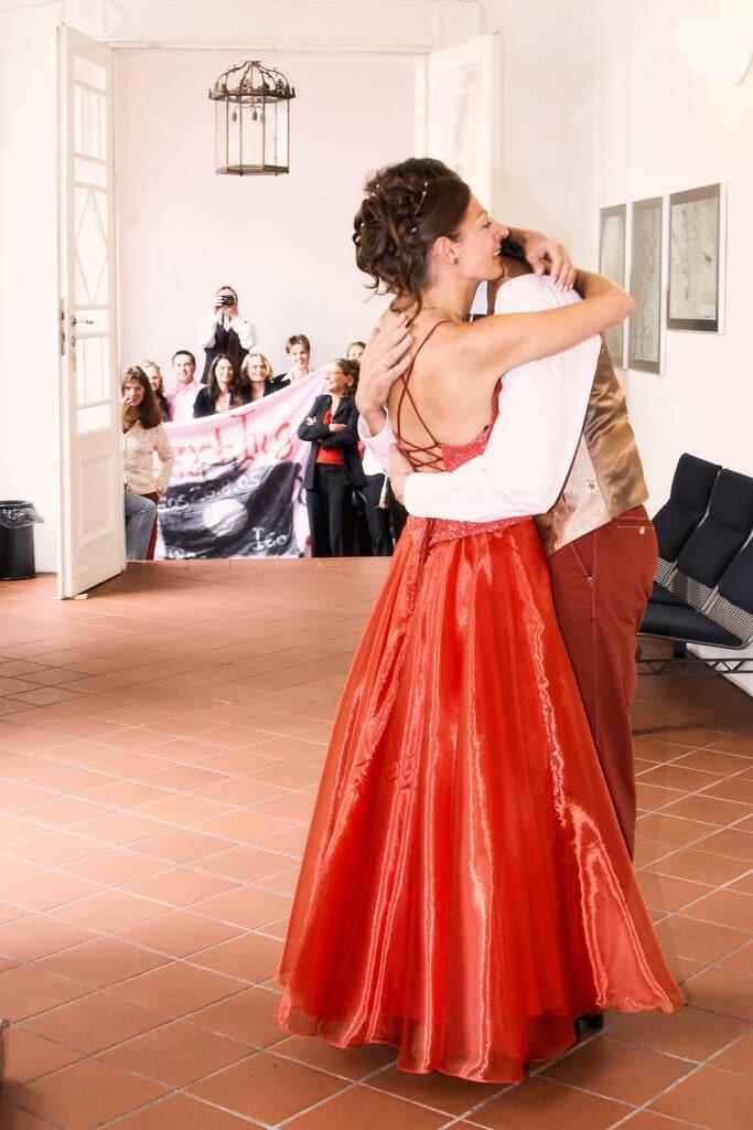Brautpaar in rot umarmt sich im Schlossflur - Celler Schloss © Hochzeitsfotograf www.hochzeitsverliebt.de