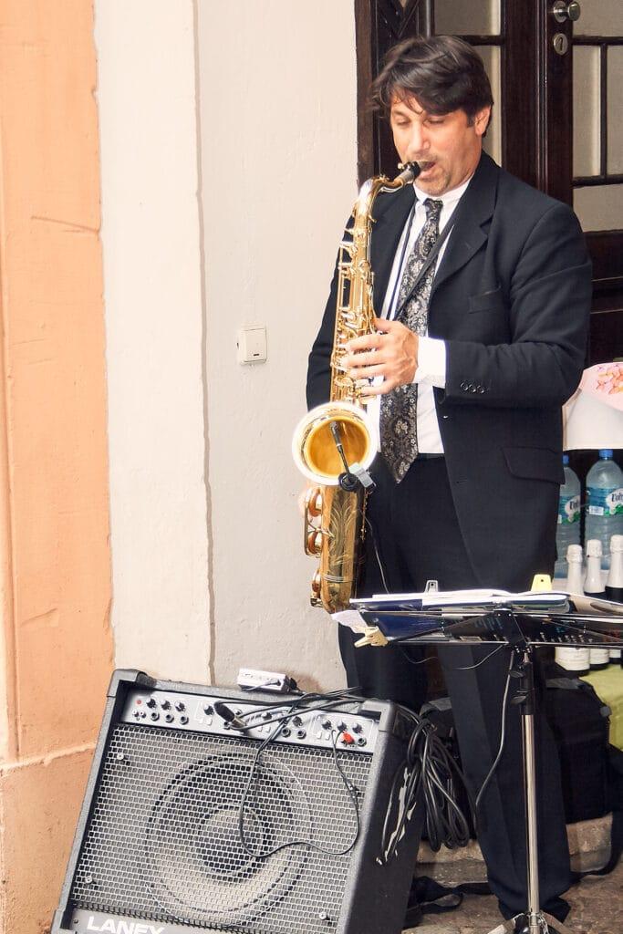Musiker mit Saxophon spielt im Schlosshof ein Hochzeitslied - Celler Schloss © Hochzeitsfotograf www.hochzeitsverliebt.de