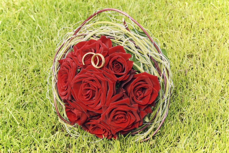 Roter Brautstrauß mit Ringen im Schlossrasen - Celler Schloss © Hochzeitsfotograf www.hochzeitsverliebt.de