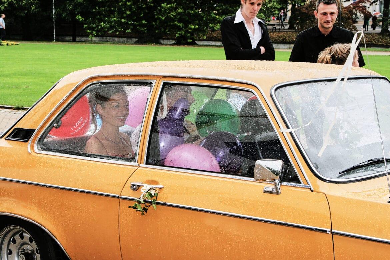 Gelbes Brautauto gefüllt mit Ballons und dem Brautpaar - Celler Schloss © Hochzeitsfotograf www.hochzeitsverliebt.de