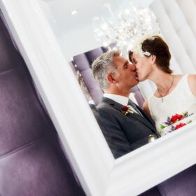 Brautpaar küssend im Spiegel zu sehen - Celler Innenstadt © Hochzeitsfotograf www.hochzeitsverliebt.de