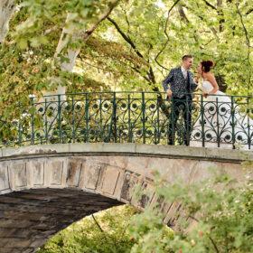 Brautpaar fröhlich an der Schwanenbrücke im Grünen - Herrenhäuser Gärten Hannover © Hochzeitsfotograf www.hochzeitsverliebt.de