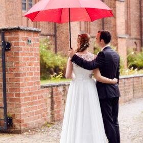 Hochzeitspaar steht mit Regenschirm an Klostermauer - © Hochzeitsfotograf www.hochzeitsverliebt.de