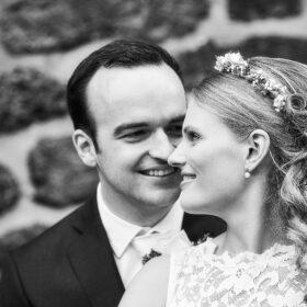 Brautpaar in schwarzweiss verliebt tuschelnd an Klostermauer - Kloster Wienhausen © Hochzeitsfotograf www.hochzeitsverliebt.de