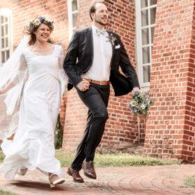 Brautpaar läuft an roter Backsteinkirche - Müden Örtze © Hochzeitsfotograf Photo Professional Misiak
