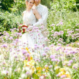 Braut und Bräutigam mitten in einer Blumenwiese - Schlosspark Celle © Hochzeitsfotograf www.hochzeitsverliebt.de