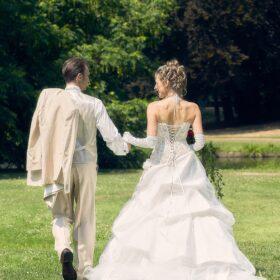 Brautpaar spaziert über den grünen Rasen - Schlosspark Celle © Hochzeitsfotograf www.hochzeitsverliebt.de
