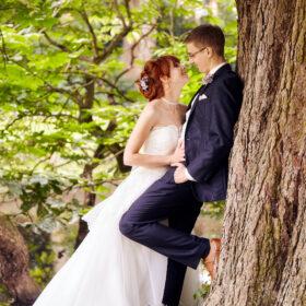 Hochzeitspärchen tuschelt am Baum - Schlosspark Celle © Hochzeitsfotograf www.hochzeitsverliebt.de