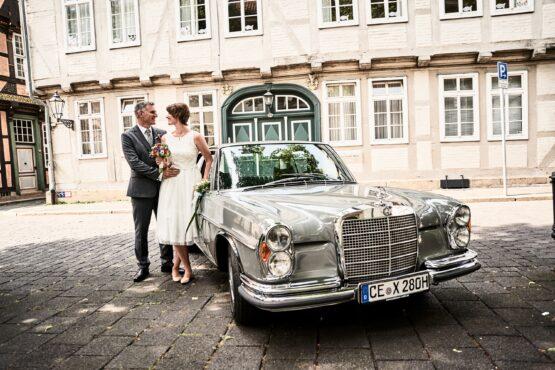 Brautpaar mit Hochzeitsauto in der Altstadt - Celler Innenstadt © Hochzeitsfotograf www.hochzeitsverliebt.de