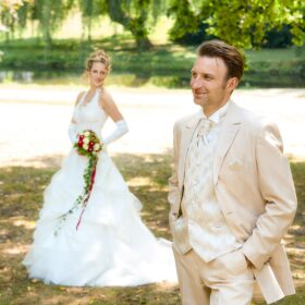 Bräutigam mit hellem Anzug steht vor der Braut im grünen - Schlosspark Celle © Hochzeitsfotograf www.hochzeitsverliebt.de