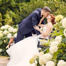 Bräutigam küsst sitzende Braut im Park - Schlosspark Celle © Hochzeitsfotograf www.hochzeitsverliebt.de