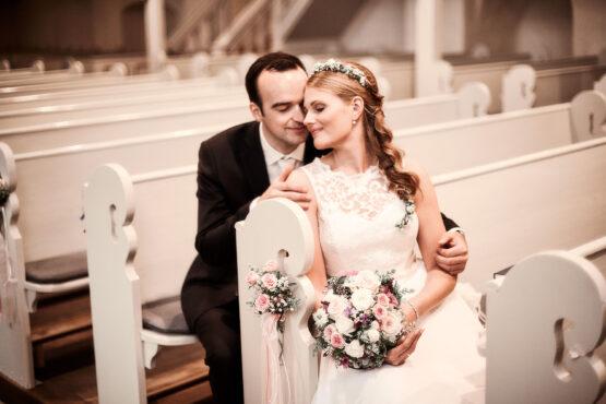 Brautpaar kuschelt auf Kirchenbank - Kloster Wienhausen © Hochzeitsfotograf www.hochzeitsverliebt.de