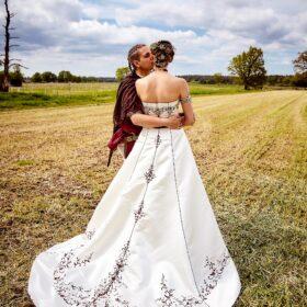 Brautpaar steht auf dem Feld und Bräutigam küsste die Braut - Lüßmanns Hof Hambühren - © Hochzeitsfotograf www.hochzeitsverliebt.de
