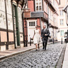 Traupaar läuft durch die enge Gasse - Celler Innenstadt © Hochzeitsfotograf www.hochzeitsverliebt.de