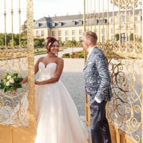 Brautpaar steht zwischen dem goldenen Tor vor dem Schloss - Herrenhäuser Gärten Hannover © Hochzeitsfotograf www.hochzeitsverliebt.de