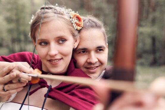 Hochzeitspaar im Mittelalterlook steht im Wald und schiesst mit Armbrust - Lüßmanns Hof Hambühren - © Hochzeitsfotograf www.hochzeitsverliebt.de