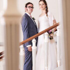 Brautpaar steht auf Treppenstufen und sieht in die Kamera - Treppenhaus Schloss Celle © Hochzeitsfotograf www.hochzeitsverliebt.de