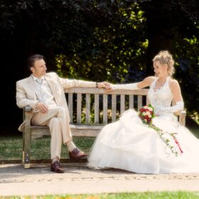 Hochzeitspaar sitzt auf der Parkbank aus Holz - Schlosspark Celle © Hochzeitsfotograf www.hochzeitsverliebt.de