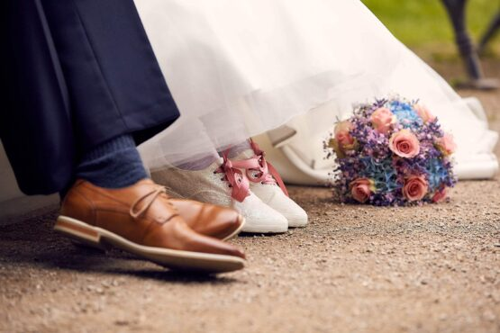 Brautpaar zeigt Schuhe und Hochzeitsstrauss - Schlosspark Celle © Hochzeitsfotograf www.hochzeitsverliebt.de