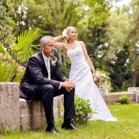 Braütigam sitzt und Braut steht an Mauer - Schloss Eldingen © Hochzeitsfotograf www.hochzeitsverliebt.de