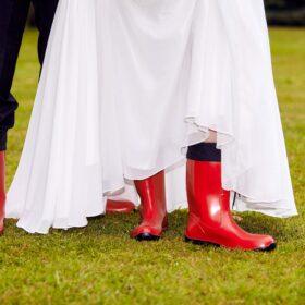 Brautpaar mit roten Gummistiefeln im Regen - Kloster Wienhausen © Hochzeitsfotograf www.hochzeitsverliebt.de