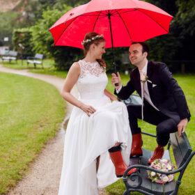 Braut und Bräutigam mit rotem Regenschirm - Kloster Wienhausen © Hochzeitsfotograf www.hochzeitsverliebt.de