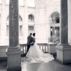 Hochzeitspaar im Schwarzweisslook umarmt sich an Innenbalustrade und schaut in die Ferne - Neues Rathaus Hannover © Hochzeitsfotograf www.hochzeitsverliebt.de