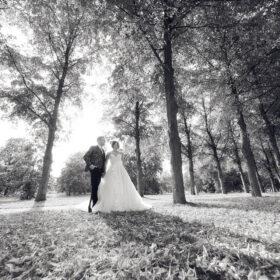 Hochzeitspaar in schwarzweiss steht im Park zwischen Bäumen - Herrenhäuser Gärten Hannover © Hochzeitsfotograf www.hochzeitsverliebt.de