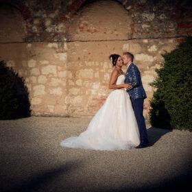 Braut wird von Bräutigam an Steinmauer auf Wange geküsst - Herrenhäuser Gärten Hannover © Hochzeitsfotograf www.hochzeitsverliebt.de