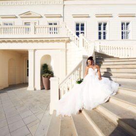 Sitzende Braut auf heller Steintreppe im Sonnenschein - Herrenhäuser Gärten Hannover © Hochzeitsfotograf www.hochzeitsverliebt.de
