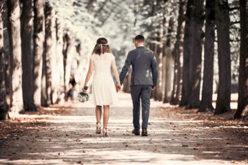 Brautpaar geht durch die Baumallee