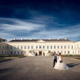 Brautpaar steht bei blauem Himmel vor dem Schloss - Herrenhäuser Gärten Hannover © Hochzeitsfotograf www.hochzeitsverliebt.de