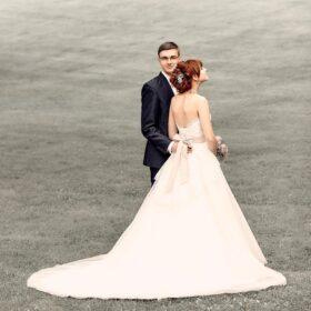 Bräutigam nähert sich der Braut auf Rasen - © Hochzeitsfotograf www.hochzeitsverliebt.de
