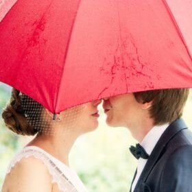 Traupaar versteckt sich unterm Regenschirm - Wildland Wietze © Hochzeitsfotograf www.hochzeitsverliebt.de