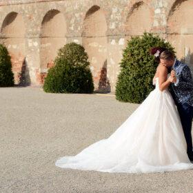 Bräutigam küsst Braut vor alter Steinmauer auf die Schulter - Herrenhäuser Gärten Hannover © Hochzeitsfotograf www.hochzeitsverliebt.de