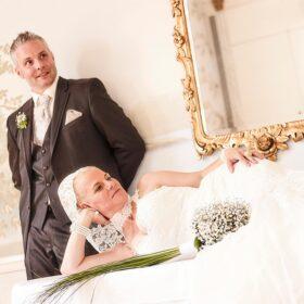 Brautpaar posiert im Hotel mit fürstlichem Stil in gold und weiss - Fürstenhof Celle © Hochzeitsfotograf www.hochzeitsverliebt.de