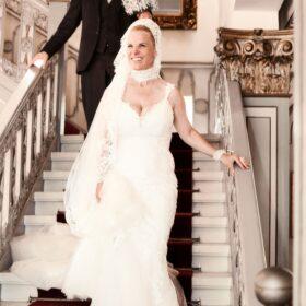 Brautpaar schreitet strahlend weisse Holztreppe herunter - Fürstenhof Celle © Hochzeitsfotograf www.hochzeitsverliebt.de