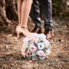 Hochzeitspaar mit Brautstrauss und Schuhen im Laub