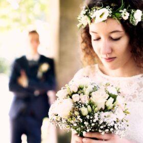 Vintagebraut schaut zu ihrem Hochzeitsstrauss hinunter