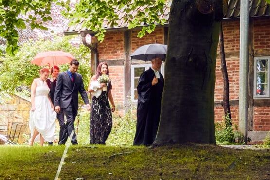 Hochzeitspaar geht im Sommerregen unter Bäumen entlang - Wildland Wietze © Hochzeitsfotograf www.hochzeitsverliebt.de