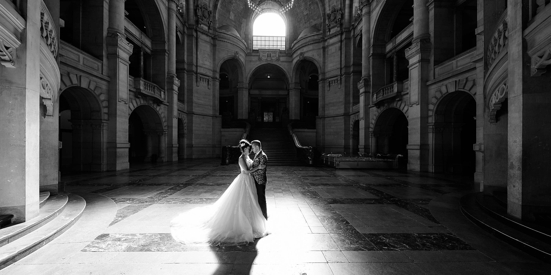 Hochzeitspaar schwarzweiss mit Licht und Schatten im prachtvollen Steinfoyer - Neues Rathaus Hannover © Hochzeitsfotograf www.hochzeitsverliebt.de