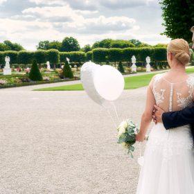 Brautpaar steht mit weißen Luftballons im Großen Garten - Herrenhäuser Gärten Hannover © Hochzeitsfotograf www.hochzeitsverliebt.de