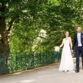 Das Hochzeitspaar spaziert über die Schwanenbrücke im Sommer - Herrenhäuser Gärten Hannover © Hochzeitsfotograf www.hochzeitsverliebt.de