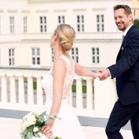 Fröhliches Brautpaar auf der Schlossterrasse mit weissem Schloss im Hintergrund - Herrenhäuser Gärten Hannover © Hochzeitsfotograf www.hochzeitsverliebt.de