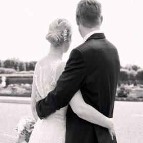 Rückenansicht von sich umarmenden Brautpaar als Halbkörperaufnahme in schwarzweiss - Herrenhäuser Gärten Hannover © Hochzeitsfotograf www.hochzeitsverliebt.de