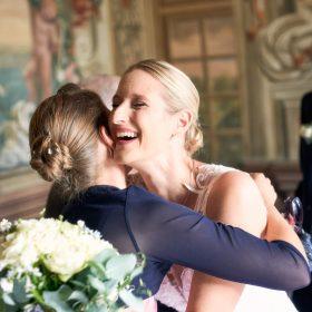 Die Braut wird umarmt und lacht in die Kamera - Frühlingszimmer Herrenhäuser Gärten Hannover © Hochzeitsfotograf www.hochzeitsverliebt.de