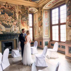 Das Brautpaar steht am Kamin des farbenfrohen Trauzimmers mit hohen Fenstern inmitten von Stühlen mit weissen Hussen - Herrenhäuser Gärten Hannover © Hochzeitsfotograf www.hochzeitsverliebt.de